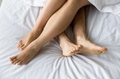 Studie: Ein Pärchen im Bett mit überkreuzten Beinen