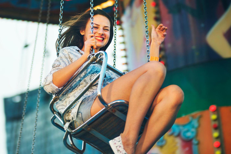 Horoskop: Eine junge Frau im Karussell auf dem Jahrmarkt