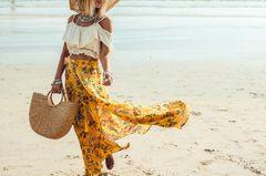 Frau am Strand mit Sommerrock und Sonnenhut und geflochtener Korbtasche