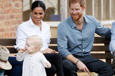 Meghan Markle und Prinz Harry schauen glücklich auf ein spielendes Kind