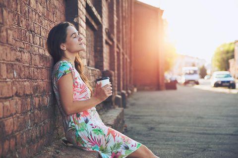 Was hilft gegen Überforderung? Eine Frau lehnt entspannt und glücklich mit geschlossenen Augen  an einer Wand