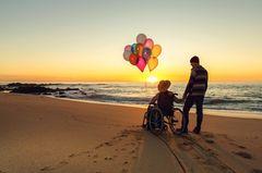 Frau im Rollstuhl mit ihrem Partner am Strand