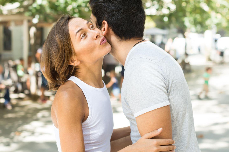 Wie kann man nett zu Leuten sein, die man nicht mag? Eine Frau umarmt distanziert einen Mann