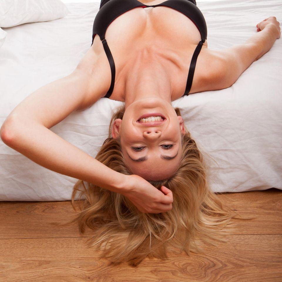 Studie: Eine junge Frau liegt im Bett und lässt den Kopf runterhängen