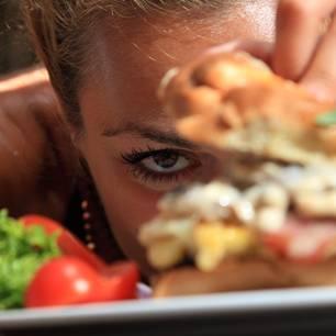 Kein Sättigungsgefühl: Frau schaut sich Burger an