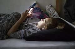 Stubenhocker: Teenager mit Handy auf dem Bett