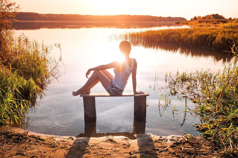 Horoskop: Eine einsame Frau sitzt vor einem See