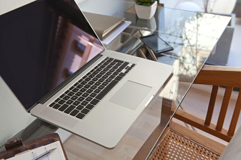 Kratzer aus Glas entfernen: Tisch mit Glasplatte, darauf stehen Laptop und Smartphone