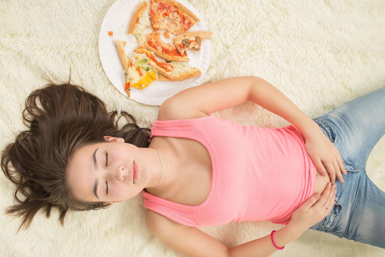 Müdigkeit nach dem Essen: Frau liegt schlafend neben Pizza