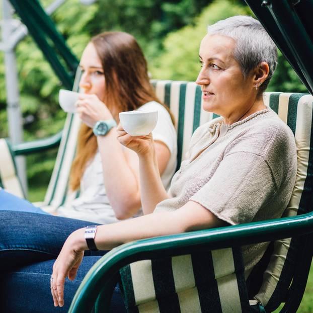 Probleme mit der Schwiegermutter: Eine junge Frau sitzt mit ihrer Schwiegermutter auf einer Bank und trinkt Tee