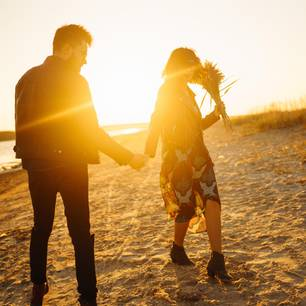 Horoskop: Ein Pärchen geht am Strand bei Sonnenuntergang spazieren