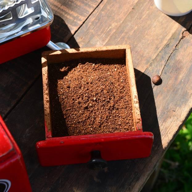 Gerüche neutralisieren: EIne rote Kaffeemühle auf einem Tisch, daneben ein Schälchen mit Kaffeepulver