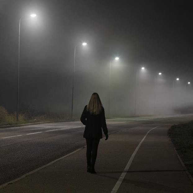 Sicherer Nachhauseweg: Frau läuft eine dunkle Straße entlang