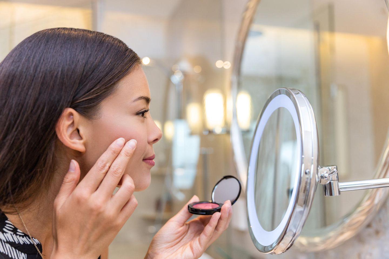die besten Beauty-Tricks aller Zeiten: Frau tupft sich Rouge auf die Wangen