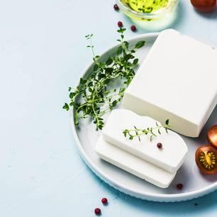 Laktosefreier Käse: Käse mit Tomaten und Kräutern auf Teller