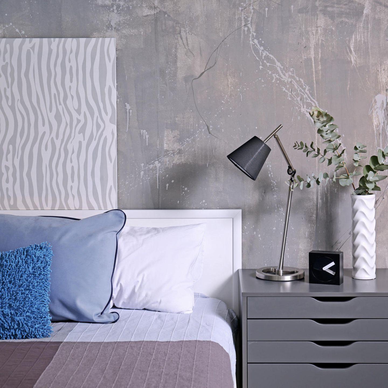 Gästezimmer einrichten: Bett mit Kissen, daneben Nachttisch mit Lampe und Vase