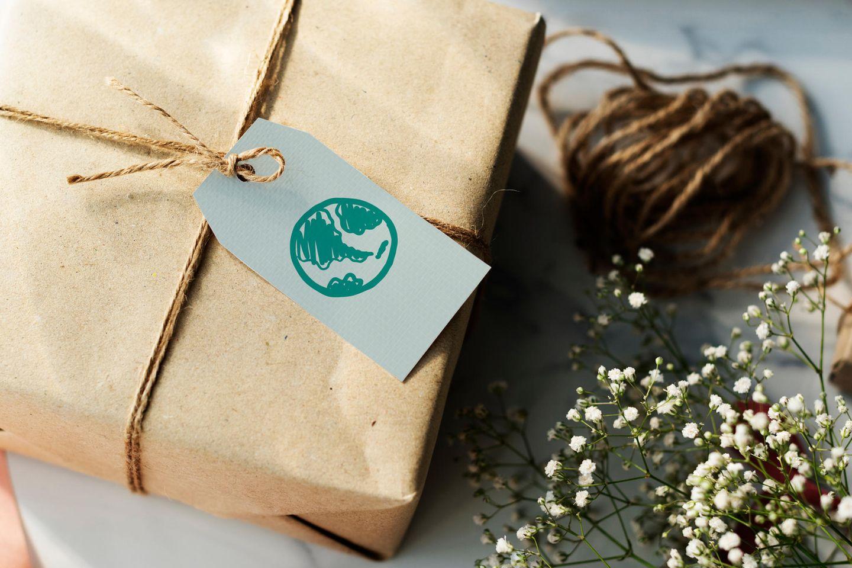 Nachhaltige Geschenke: Geschenk in Packpapier gewickelt, daneben Packband und Schleierkraut
