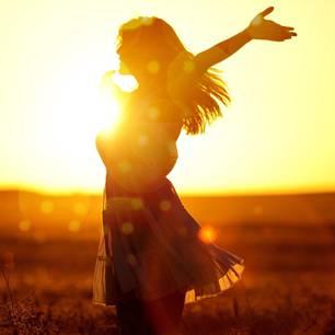 Horoskop: Eine Frau freut mit ausgebreiteten Armen im Sonnenaufgang