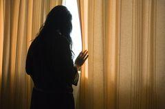 Psychische Erkrankungen: Frau am Vorhang