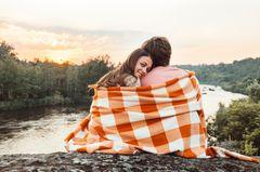 Welches Sternzeichen passt zu Steinbock? Ein Pärchen auf einer Klippe am See in eine Decke gehüllt