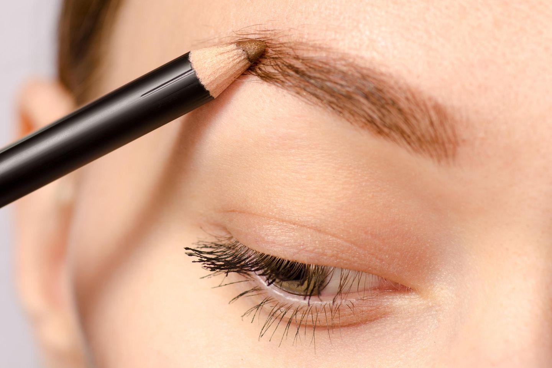 Perfekte Augenbrauen: Frau malt Augenbrauen nach