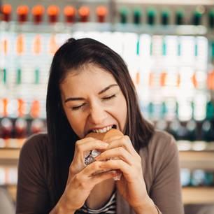 Binge Eating: Frau stopft Essen in sich hinein