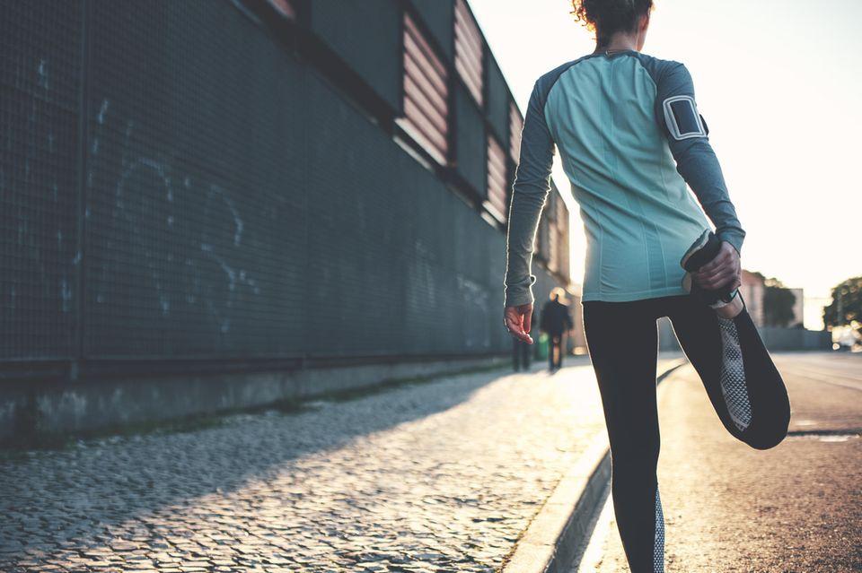 Muskelkater vorbeugen: Frau dehnt sich