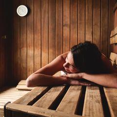 Nackt in der Sauna: Frau sauniert im Liegen