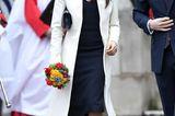 Ohne Babybauch, dafür wie immer super stylisch: Der weiße Mantel ist der perfekte Kontrast zu Meghans schwarzemMidikleid.