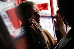 Hassliebe: Ein Mann und eine Frau berühren sich durch eine Glasscheibe getrennt