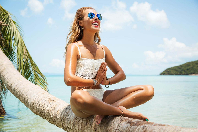 Make-up-Fehler bei Hitze: Frau sitzt auf einem Baumstamm am Meer