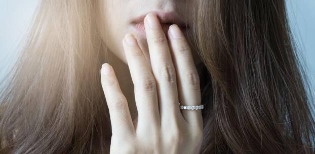 Mundgeruch: Frau hält sich die Hand vor den Mund