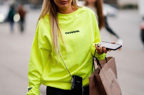Neon im Alltag stylen: Frau im neonfarbenen Pullover