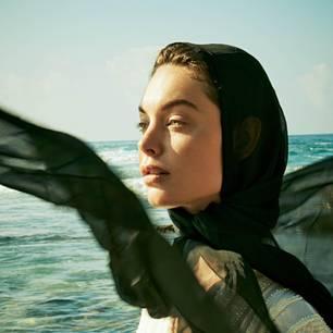 Wirkstoffe aus dem Meer: Frau mit Tuch am Meer