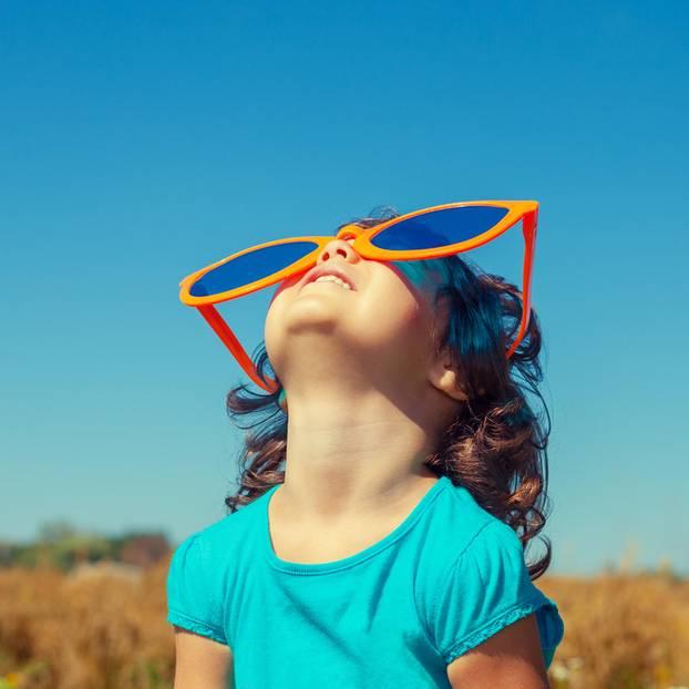 Sinn des Lebens: Ein Kind schaut mit riesiger Sonnenbrille auf der Nase in den Himmel