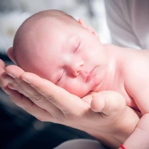 Frau hält Baby in ihren Händen