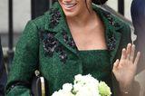 Meghan Markle winkt und trägt Blumen