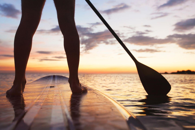 Freizeitaktivitäten: Frau macht Stand-Up-Paddling bei Sonnenuntergang