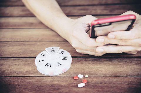 Pille zu spät genommen: Eine Frau mit Handy in der Hand und einer Pillenschachtel