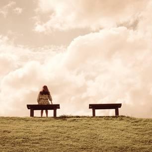 Warum finde ich nicht die große Liebe? Eine Frau sitzt allein auf einer Bank