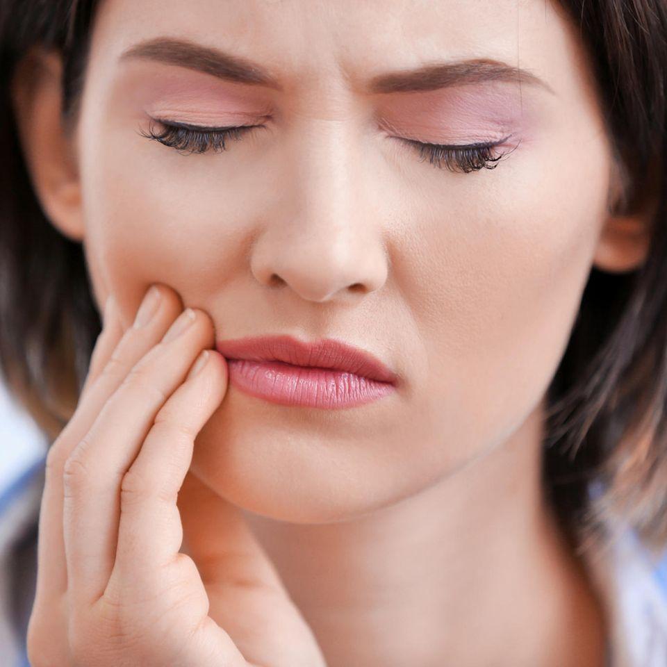 Zahnschmerzen Hausmittel: Frau hält sich die Wange