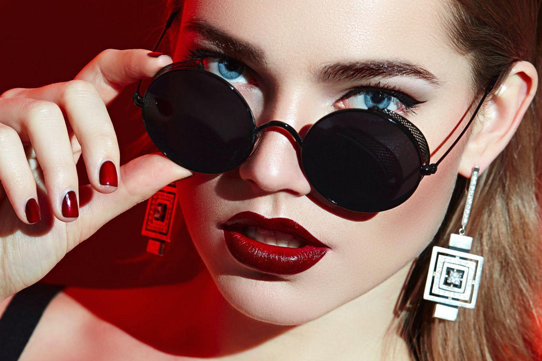 Model mit dunkelrotem Lippenstift und Sonnenbrille, blauen Augen, rotem Nagellack