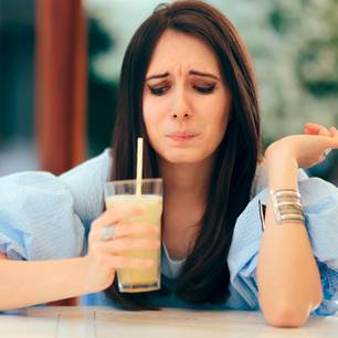 Was sagt es über Menschen aus, wenn sie jammern? Eine jammernde Frau mit Smoothie in der Hand