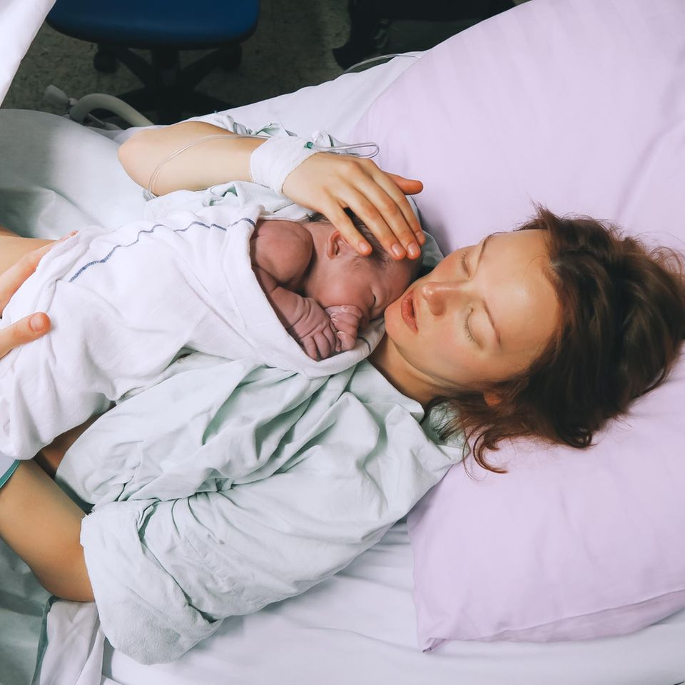 Dammriss: Mutter mit neugeborenem Baby im Kreissaal
