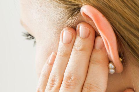Ohrenschmerzen: Frau fasst sich ans Ohr
