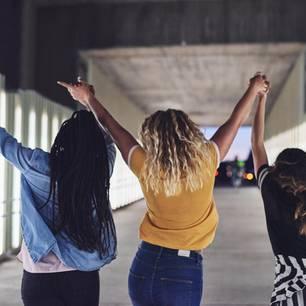 Dinge, die nur selbstbewussten Menschen helfen: Drei Frauen laufen mit hoch gestreckten Händen durch einen Tunnel