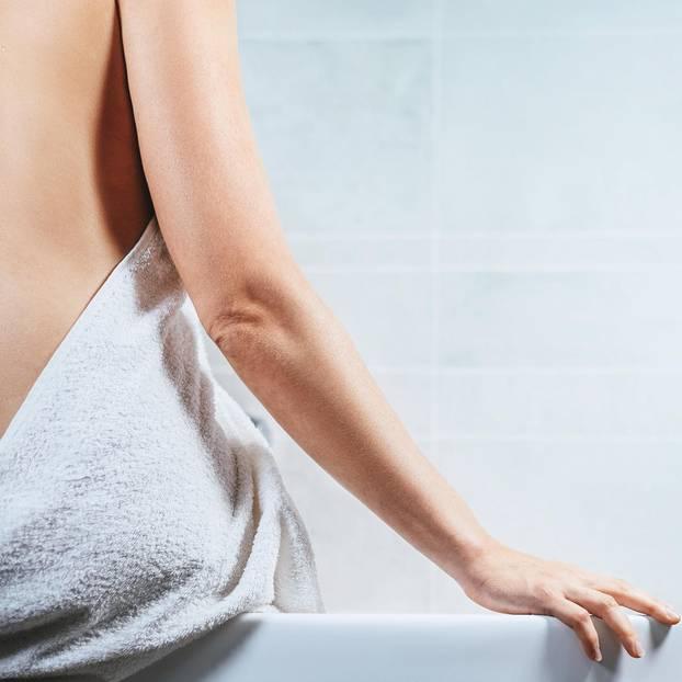 Feigwarzen behandeln: Frau mit Handtuch um den Hüften