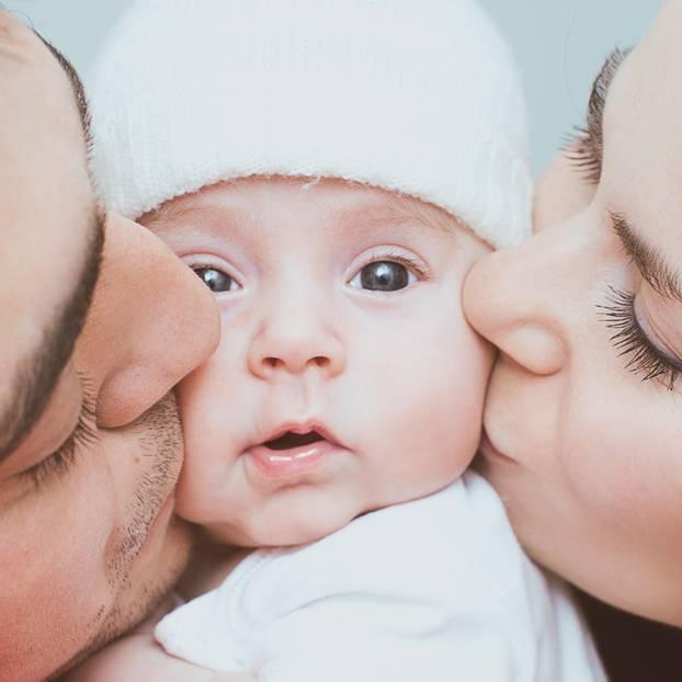 Was macht die Elternzeit mit der Beziehung: Eltern küssen Baby