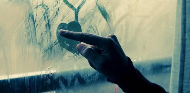 Broken-Heart-Syndrom: Frau zeichnet Herzen auf Glas