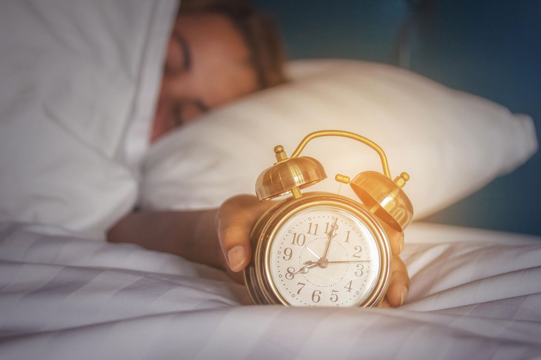 Snooze-Taste: Frau umfasst Wecker